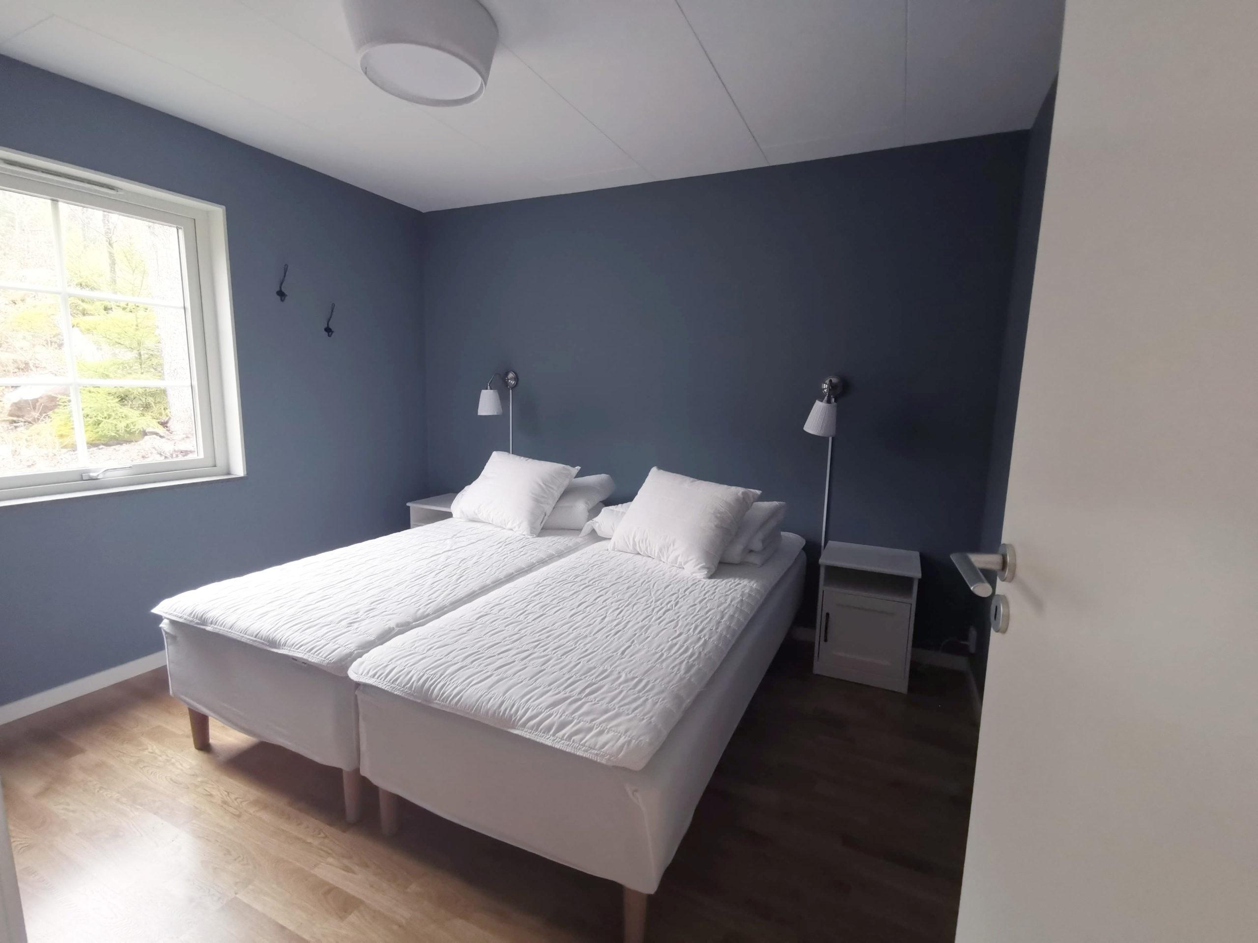 Bild på sovrum med dubbelsäng i stuga på Basunda Gård